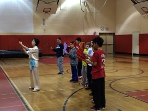 Master Lin  teaches HBT students basic Tai Chi Fan moves.
